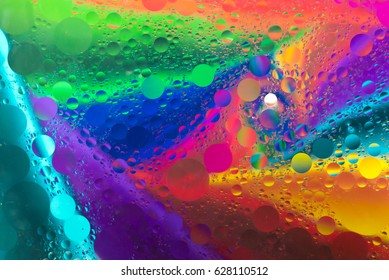 Rainbow background with oil spot bubbles on water surface with smoke pattern
