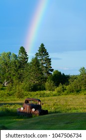 Rainbow behind weathered rusty truck in field in down east Maine on a summer day.