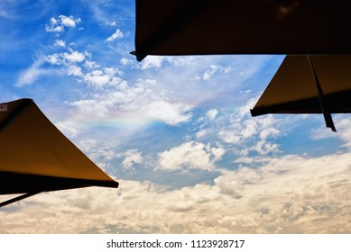 Rainbow between the umbrellas in summer in Framura - Liguria - Italy