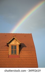Rainbow beyond a reddish roof of a house