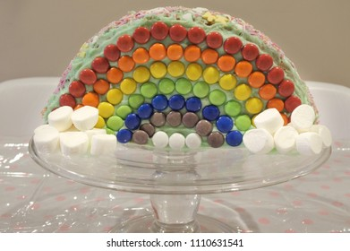 Rainbow birthday cake on cake stand with marshmallows and colorful lollie. Food background and texture.