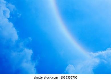 rainbow in blue sky background