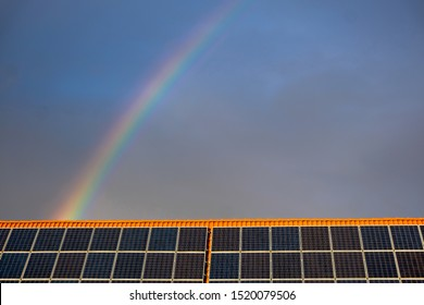 Rainbow in the blue sky over a house roof with solar panels