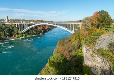 Rainbow bridge between USA and Canada and surrounding Niagara river shore near Niagara Falls in a sunny autumn day