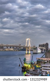 Rainbow Bridge with Cargo and cruise ships moored or sailing in Odaiba Bay of Tokyo.