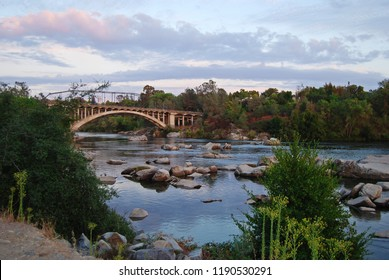 Rainbow Bridge in Folsom California in the early morning with green trees along the river banks and big boulders reflecting in the water