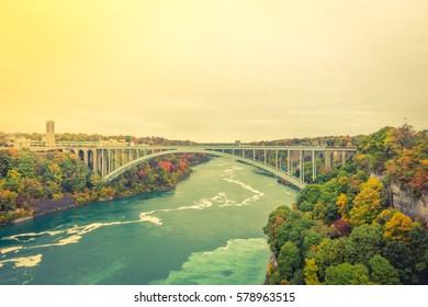 Rainbow Bridge at Niagara Falls during sunrise  ( Filtered image processed vintage effect. )