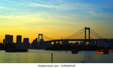 Rainbow bridge and sightseeing ships seen from Odaiba seaside park Tokyo