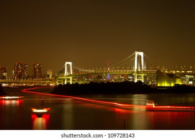 Rainbow bridge in tokyo with long light trail of boat