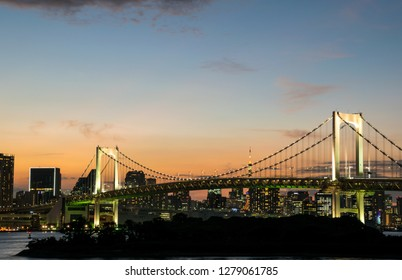 The Rainbow Bridge at Tokyo on a evening time with the sunset light on the sky and the view of Tokyo City as a background.