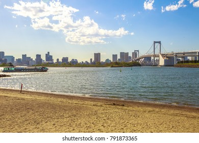 Rainbow Bridge with Tokyo Skyline from Odaiba Seaside Park in Odaiba Island, Japan. A tourist ferry connecting Tokyo with Daiba Island on background. The Rainbow Bridge is a modern and iconic landmark