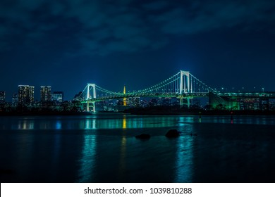 rainbow bridge and tokyo tower take view from odaiba  in the sunset