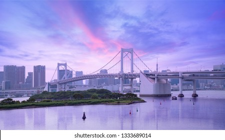 rainbow bridge and urban skyline at sunset, Tokyo, Japan