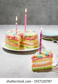 Rainbow cake decorated with festive candles on a gray background. A cut - off piece of birthday cake. Festive mood. Three years old. Space for text. Copy space. Colorful children's dessert. Holiday.