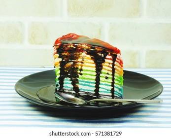 rainbow cake slice with chocolate sauce