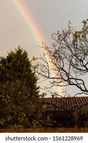Rainbow cast over suburban house.