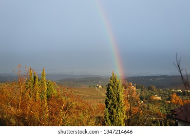 Rainbow in the characteristic landscape of Tuscany: hills, farmhouses, olive trees, cypresses, vineyards