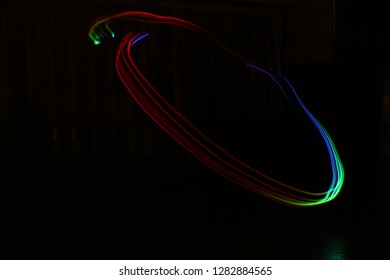 A rainbow circle floats on a black background