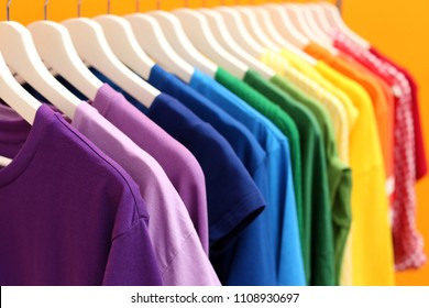 Rainbow clothes on hangers against color background, closeup