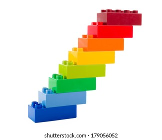 A rainbow color lego blocks in the form of stairs on white background