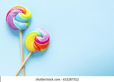 rainbow color lollipops on blue background