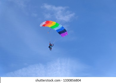 Rainbow color parachute is in the blue sky.