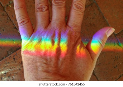Rainbow color spectrum light on the back of a hand