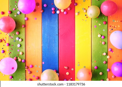 Rainbow colored carnival background with copy space surrounded by colorful party balloons, candy and confetti