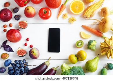 Rainbow colored fruits and vegetables on a white table and a cellphone. Fruit and veggies delivery concept. Top view.