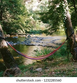 Rainbow colored hammock over stream in Ardeche, France