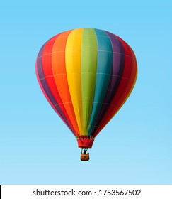 Rainbow colored hot-air balloon floating against a blue sky. Pilot in silhouette.