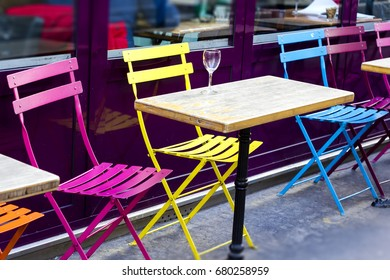 Rainbow colored metal chairs on the cafe patio in Paris, France
