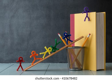 Rainbow colored pipe cleaner people stand and climb ready for learning. With an antique black board and natural window light this is delightful for a variety of educational ideas and concepts