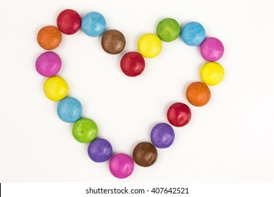 rainbow colored sugar coated candies in heart shape