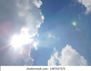 Rainbow Colored Sun Dog in the Heavenly Looking Deep Bright Blue Sky with the Sun Shining through Big White Clouds Casting Beams of Bright Light across the Day Time Sky