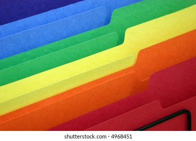 rainbow colored tabbed file folders in a basket