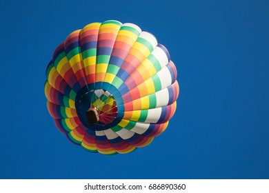 Rainbow colored tear drop shaped hot air balloon and balloon basket with cloudless blue sky from below