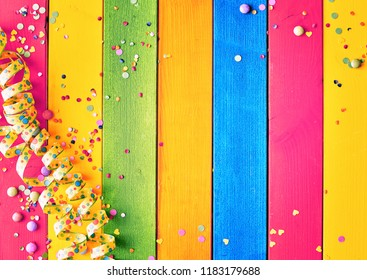 Rainbow colored wood carnival background with coiled streamers, scattered confetti and sugared candy around central blank copy space
