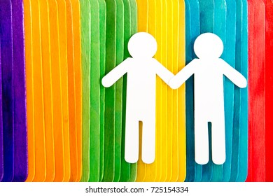 Rainbow colored wooden sticks in a row with white carboard male figures - symbolising gay marriage or partnership