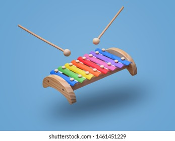 Rainbow colored wooden toy xylophone hovers in the air with two sticks. Isolated on light blue background
