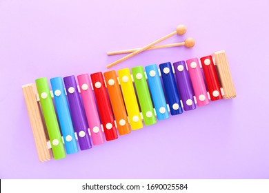 Rainbow colored wooden toy xylophone with two sticks on purple background. Top view