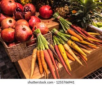 Rainbow colorful carrots and pomegranates on farm market