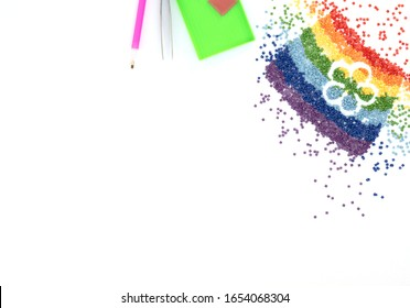 The rainbow of colorful crystals with flower shape, tweezers, stylus and tray for diamond embroidery, mosaic on white background. Handmade hobby concept. Flat lay style with copy space for your text.