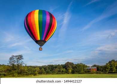 Rainbow colorful hot-air balloon floats on a summer morning with bright blue sky