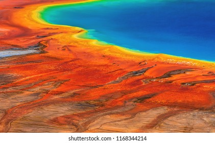 A rainbow of colors presented in the form of microbial mats surrounding Grand Prismatic Spring in the Midway Geyser Basin of Yellowstone National Park, Wyoming, USA.