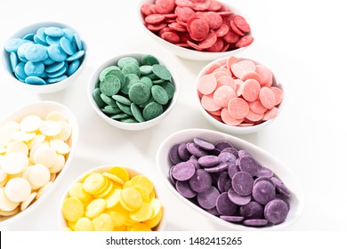 Rainbow colors of round chocolate chips in a white bowls for melting chocolate shapes on a white background.