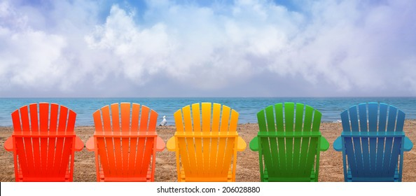 A rainbow of colors of wooden beach chairs are lined up along the water shore. There is copyspace in the clouds for a vacation message.