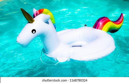 Rainbow coloured inflatable unicorn floating in a swimming pool in the summer, vivid blue water with contrasting white and multicolored unicorn