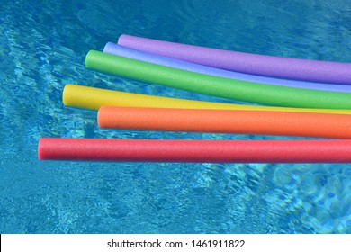 Rainbow coloured pool noodles floating in a swimming pool. Fun summer vibes.