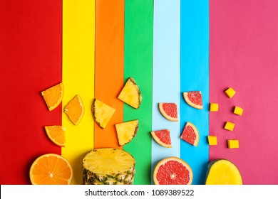Rainbow composition with fresh fruits on color background, flat lay